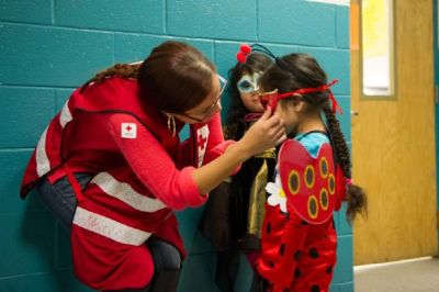 Red Cross volunteer Lilliana Matos helps Ferndanda Velasco with her mask, as sister Maria Velasco looks on. (Photo by Jason Colston/American Red Cross)